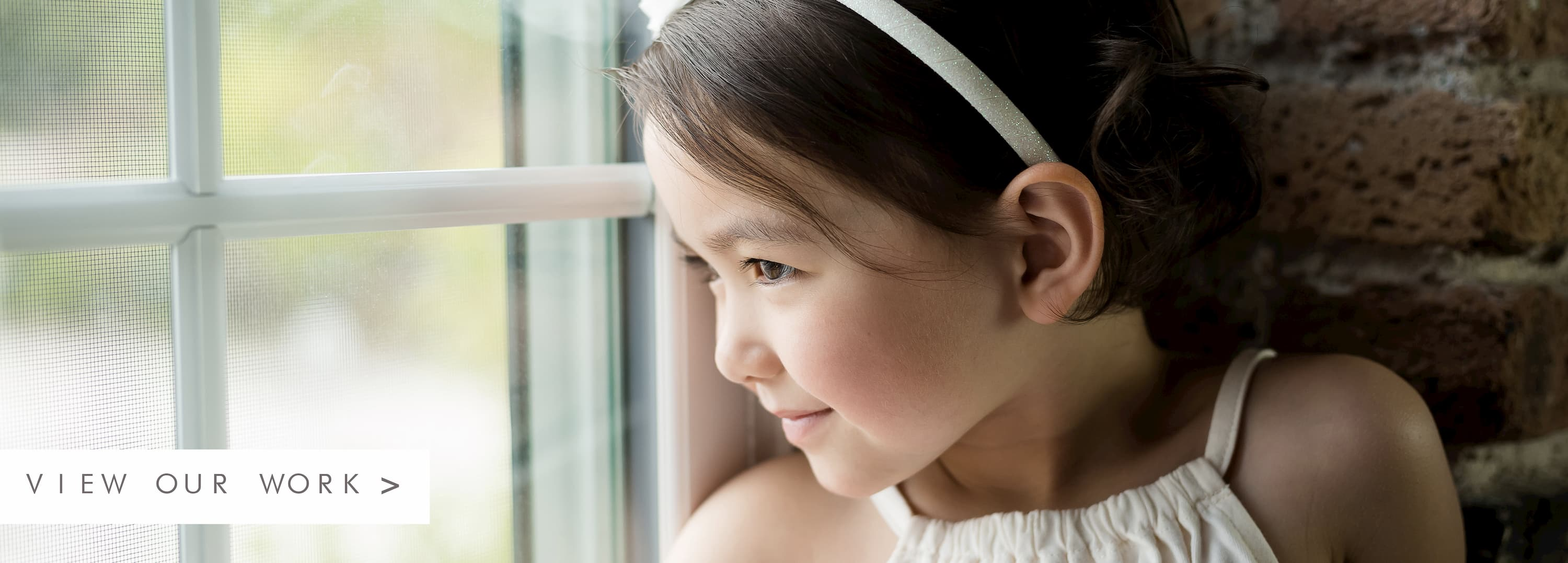 A child with rosy cheeks and a white headband in front of a brick wall looking out a window. To the left there is text to view our work